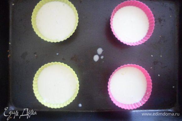 Разлить получившуюся массу по формочкам, поставить и на противень. Нагреть духовку до 160 градусов, поставить на низ духовки емкость с водой и поставить на решетку наши формочки.