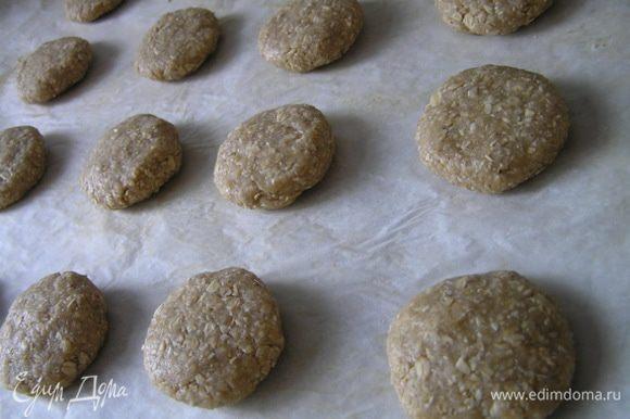 Из получившейся массы сформировать шарики размером чуть больше грецкого ореха, затем их приплюснуть и выложить на противень для выпечки, застеленный кулинарной бумагой.