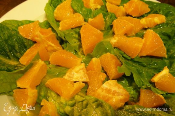 На тарелку выкладываем салатные листья. На них апельсин.