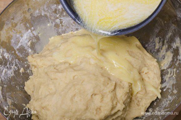 В готовое тесто вливаем постепенно небольшими порциями теплое жидкое сливочное масло, вымешиваем.