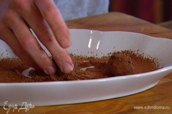 Набирать остывшую шоколадную массу ложкой, руками формировать небольшие шарики и обваливать в какао.