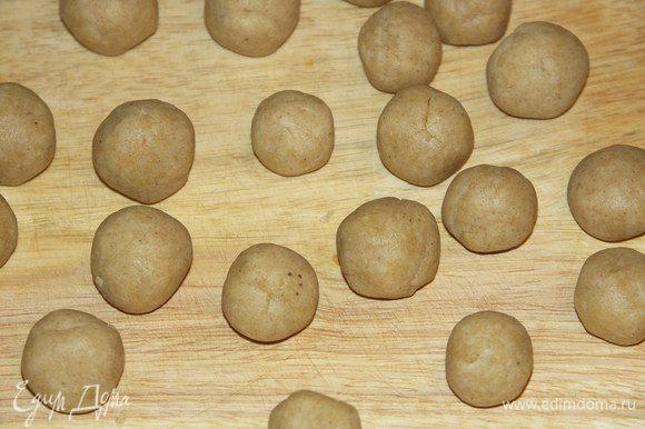 Разделить тесто на 2 половинки.Одну снова завернуть в плёнку и убрать в холод.И второй скатать 20 шариков...