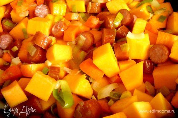 Все овощи нарезать кубиками. В глубоком сотейнике обжарить на растительном масле два вида лука и чеснок,затем-кусочки моркови и после тыквы. Готовить до полуготовности тыквы. Добавить нарезанные на кусочки охотничьи колбаски и курицу, а затем немного растолчённые в ступке специи; тушить 5-7 минут.