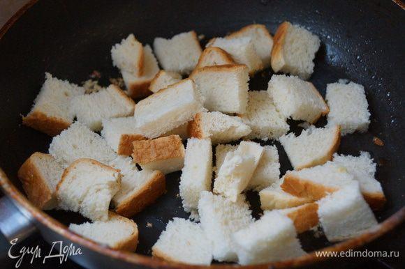 Порезать хлеб кубиками 1х1 см. Налить в сковороду масла, ароматизировать его чесноком (выдавить чеснок). Закинуть хлеб.