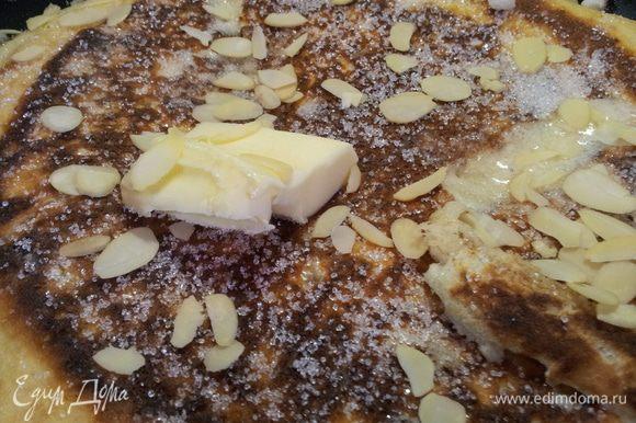 Через минуту добавляем ложку сливочного масла, посыпаем сахаром и миндальными хлопьями. Разрезаем на несколько кусочков и помешивая жарим 3-5 минут. В конце посыпаем сахарной пудрой.