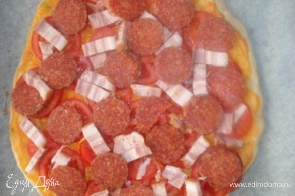 Затем слоем выложить кружочки помидоров, порезанный брусочками бекон и порезанную кружочками колбасу