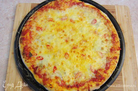 Разогрейте духовку до максимальной температуры. Поставьте в самый низ решетку. Когда печь прогреется - поставьте на решетку пиццу. Выпекайте 7-10 минут (у меня - около 12 минут). За 3 минуты до конца запекания, посыпьте пиццу Пармезаном. Когда сыр подрумянится и снизу пиццы появится аппетитная корочка - снимайте пиццу с огня. Выложите пиццу на блюдо и полейте слегка оливковым маслом. Поперчите пиццу и положите свежие листья базилика.