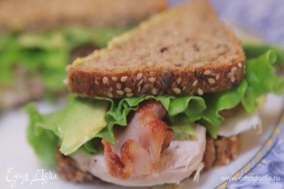 Смазать оба куска хлеба небольшим количеством майонеза. На один выложить куриное мясо, авокадо, бекон и листья салата, смазать майонезом и накрыть вторым куском хлеба. Плотно сжать бутерброд руками.