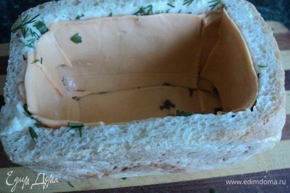 Смазать стенки и дно хлеба внутри тонким слоем мягкого плавленого сыра, посыпать зеленью и выложить пластинками сыра.