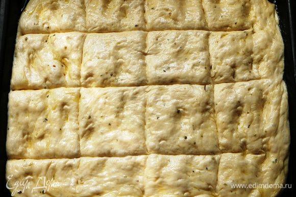 Достаем тесто из миски, обминаем его и придаем фокачче нужную форму. У меня традиционная лепешка. Выкладываем ее на противень, смазанный растительным маслом и оставляем на расстойку на 40 минут. Сделать на лепешке бороздки, смазать оливковым маслом.