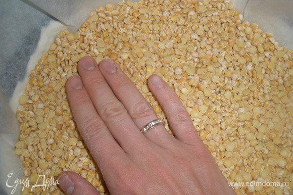 На тесто выложить лист пергамента и всыпать сухой горох или фасоль. Благодаря этому, тесто не будет подниматься. Отправить в духовку на 15 минут при температуре 200 градусов.