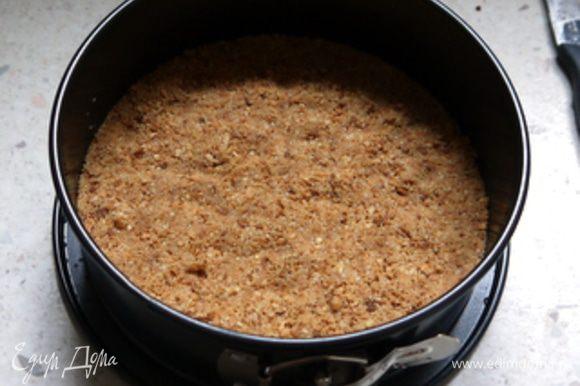 Форму для торта с разъёмным бортом 18 см в диаметре накрыть листом пергамента по размеру и смазать маслом. Выложить смесь печенья с маслом и хорошо утрамбовать. Убрать в холодильник на 30 минут.