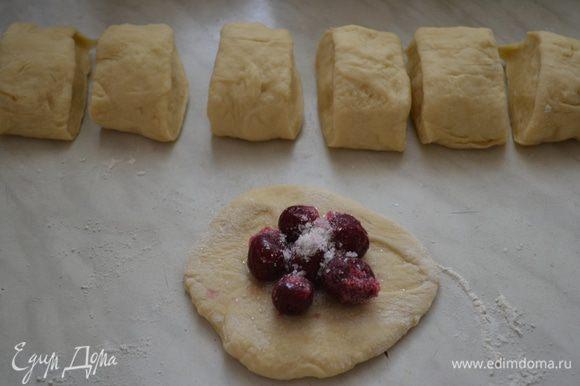 Затем еще раз хорошо вымешиваем, разделяем на 2 части, раскатываем в колбаску, делим на части, раскатать не тонко в лепешку, положить прямо замороженные вишни, присыпать сахаром, защипнуть края, и укладываем на сковородку с толстым дном, швом вниз, не сильно плотно, смазать желтком, выпекать при 190 гр 30 мин.