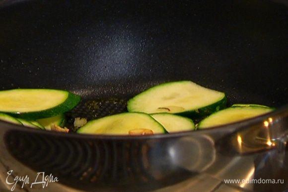 Разогреть в глубокой сковороде оливковое масло, выложить чеснок и цукини и обжарить до легкого золотистого цвета.