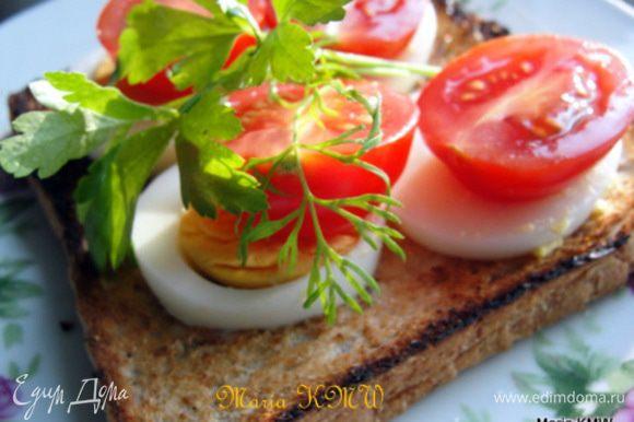 Зубчики чеснока разрезать на половинки и ими натереть ещё горячий хлебушек. Смазать майонезом, уложить на хлебцы яйца, помидорки, поперчить, посолить и украсить зеленью. Приятного аппетита.