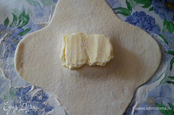 Раскатать тесто в виде своеобразного плюса и положить на середину отбитое масло