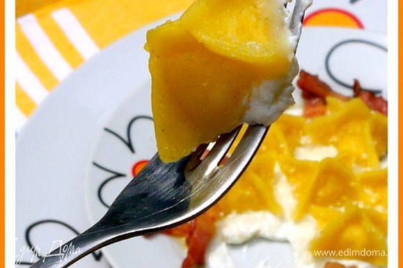 Отварить равиоли в подсолённой воде, слить, выложить на сливочный крем и разложить вокруг жареные копчёности. Посыпать сыром, поперчить и подать на стол.