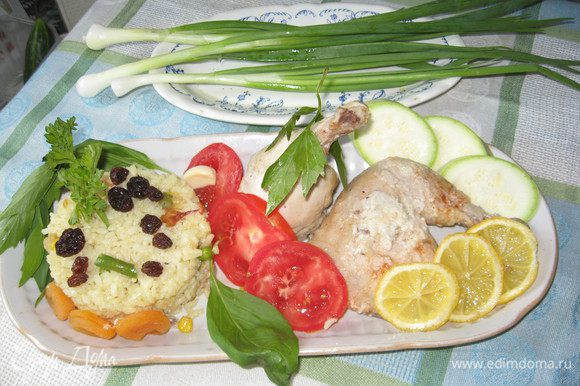 Подаём блюдо. Для этого на продолговатое блюдо формируем из риса через кольцо не высокую пирамидку. В моём случае (через салатное кольцо!) Затем формирую не высокую таблеточку и украшаю зеленью. Дополняем для вкуса 3 шт. кураги и 5 шт. изюма. Кладём окорочка. обкладываем помидорами, кружками молодого кабачка. Кладём в стороне перья лука. Есть вариант рядом с дольками глазурированного лимона. Приятного аппетита. Курица так сочна и приятна на вкус. Съедается в один миг!