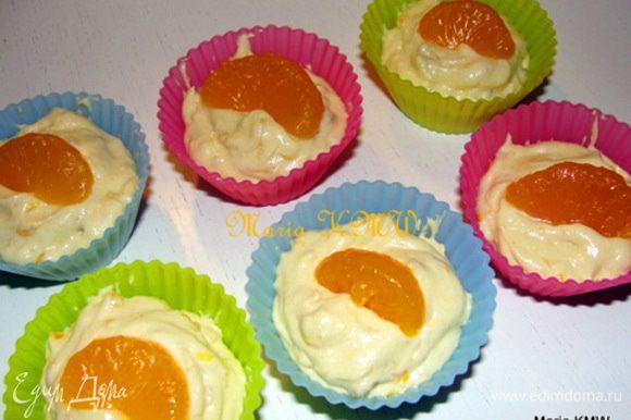 Однородное тесто выложить в смазанные формочки, сверху украсить кусочками оставшихся мандаринок. Выпекать 25 минут в разогретой до 200 С духовке.