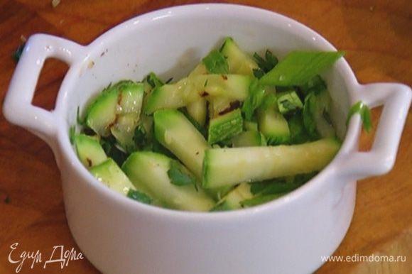 Две небольшие керамические формы смазать оливковым маслом, выложить в них кабачки с зеленью.