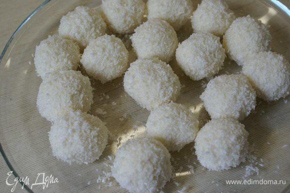 Ложкой брать одинаковое количество творожно-кокосовой массы и лепить шарики, не забывая про начинку. Обвалять в кокосовой стружке. Поставить в морозильник на минут 15 и подавать к столу.
