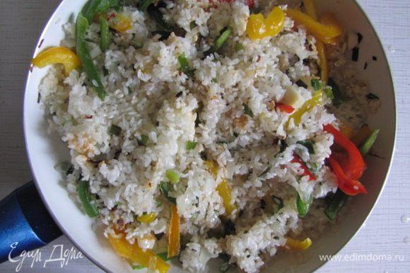 Рис тщательно промыть, слить воду, добавить в сковороду с луком и чесноком. Рис немного прожарить до легкой прозрачности. Добавить порезанный болгарский перец, острый перец и натертую на терке морковь.(Морковь - не обязательный ингредиент). Помешивая, потомить еще минут 7.