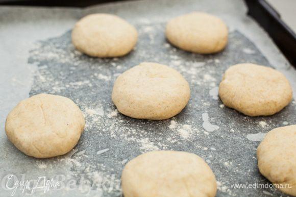 Когда тесто поднялось второй раз, сформировать из него небольшие плоские булочки, примерно 7-8 см в диаметре. Выложить их на смазанный маслом, застеленный пергаментом противень и присыпанный мукой противень. Оставить минут на 15 для расстойки.