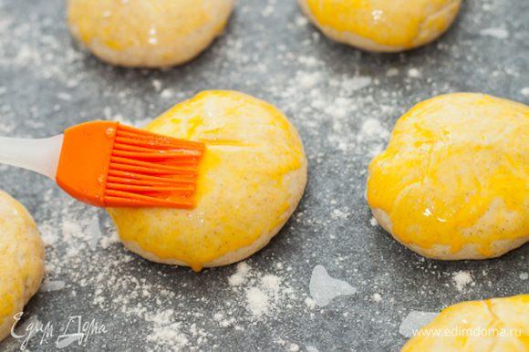 Теперь смазать булочки желтком, сделать на них глубокие крестообразные надрезы.