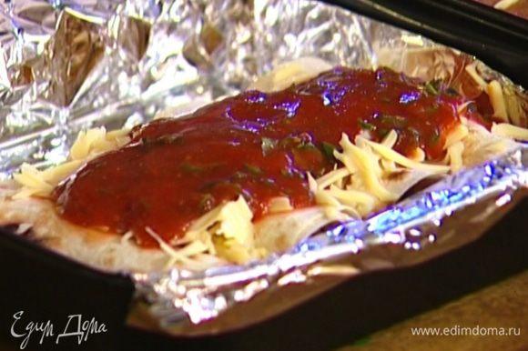 Глубокий противень застелить фольгой, уложить в него буррито, присыпать сверху оставшимся сыром, полить соусом и отправить в разогретую духовку на 15 минут.