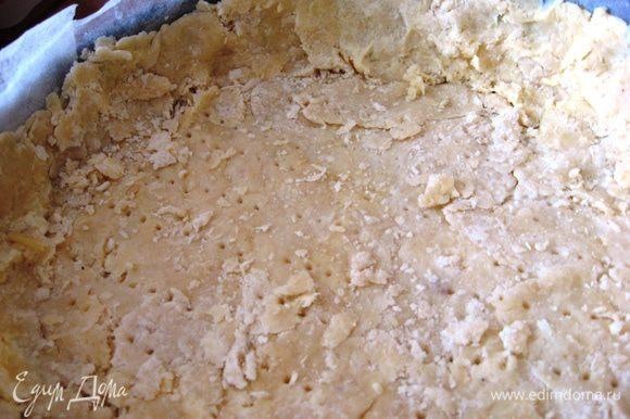 Форму для выпечки выстилаем пергаментной бумагой. Выкладываем раскатанное тесто, делаем бортики. Вилочкой делаем дырочки. Выпекаем в духовке 15 минут при 180 градусах.