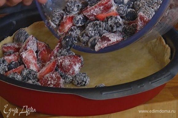 Достать форму из духовки, убрать бумагу с горохом, выложить на корж ягоды и выпекать пирог еще 20 минут.