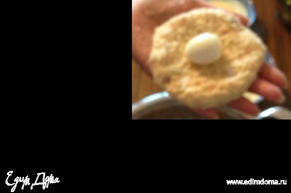 Из полученной массы сформировать пласт толщиной в 1 см, на середину положить перепелиное яйцо. защипать края
