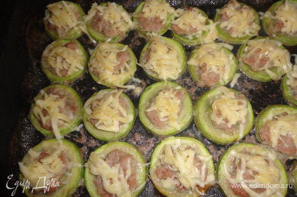 За 5 минут до готовности вынуть противень из духовки и посыпать кабачки тертым сыром.