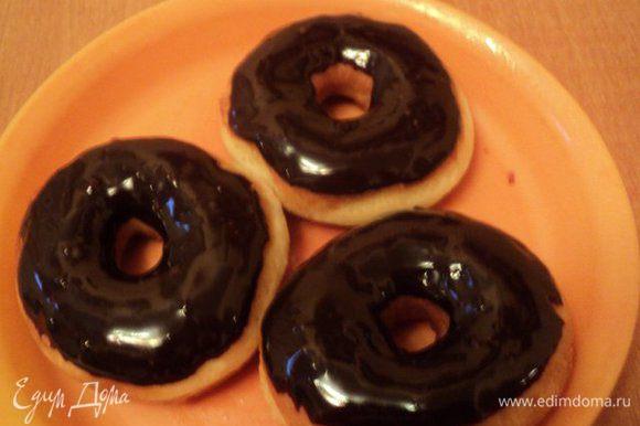 Остывшие донетсы окунуть с одной стороны в шоколад и выложить на блюдо. Для быстрого застывания глазури можно поставить их холодильник на 5-10 мин.