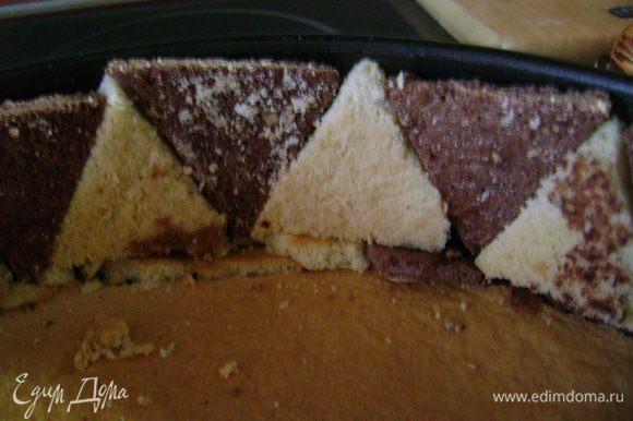 На дно разъемной формы выложить бисквит, который выпекался в этой форме. Край выложить треугольниками, чередуя белый с коричневым.