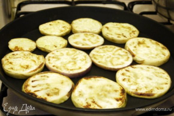 Пока запекается перец, нарезать баклажаны на кружки по 0,5 см и обжарить их или на гриле или на сковороде с антипригарным покрытием, смазав оливковым маслом с обеих сторон.