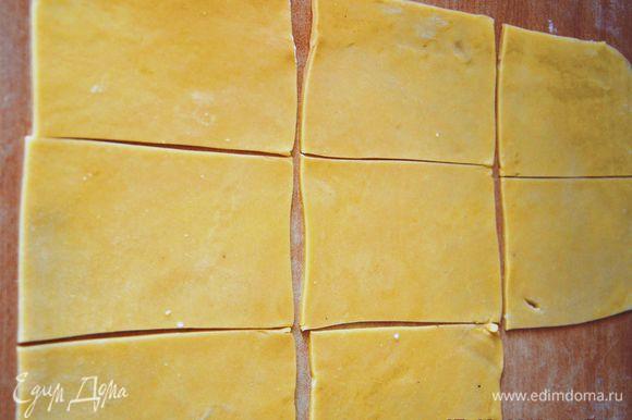 Тесто тонко раскатать на слегка присыпанной мукой поверхности. Нарезать прямоугольниками размером примерно 12*8 см.