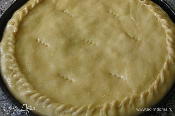 Оставшееся тесто (1/4 часть) раскатать в круг меньшего диаметра, при помощи скалки перетащить его на пирог сверху и защипить края. Смазать пирог растопленным сливочным маслом и наколоть в нескольких местах вилкой
