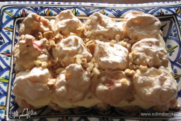 Выложить второй ярус меренгами, посыпать орехами и смазать кремом.