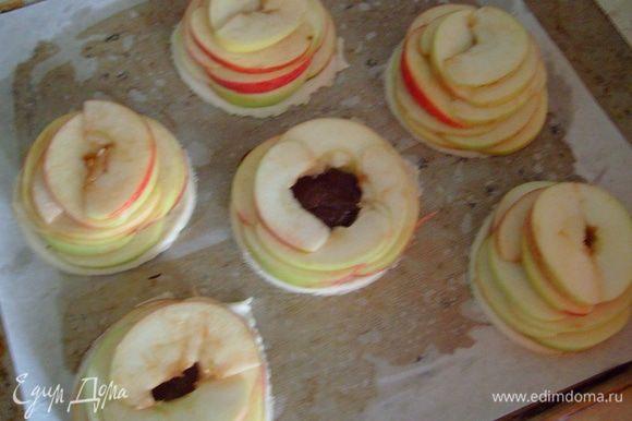 Яблоки откинуть на дуршлаг. А затем выложить их сверху на тесто. Выкладывать нужно по кругу, как бы создавая пирамидку. (Фото не очень качественное, но думаю идея Вам понятна). Сверху яблоки посыпать сахаром (примерно 1 ч. л. на одно пирожное) и положить по небольшому кусочку сливочного масла. Выпекать пирожные в разогретой до 180 градусов духовке 20-25 минут.