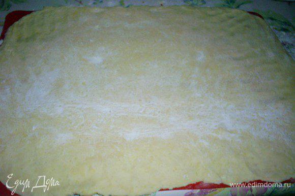Посыпаем тесто и рабочую поверхность мукой, раскатываем наше тесто в прямоугольный пласт толщиной около 5 миллиметров. Это удобно делать на силиконовом коврике или бумаге для выпечки. Снова посыпаем пласт теста мукой.