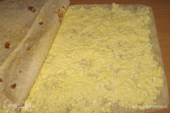 На один лист лаваша равномерно распределить творожную начинку. Сверху накрыть вторым листом и начинаем сворачивать рулет.