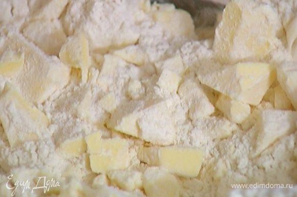 Предварительно охлажденное сливочное масло нарезать кубиками, соединить с мукой и солью и порубить в крошку.