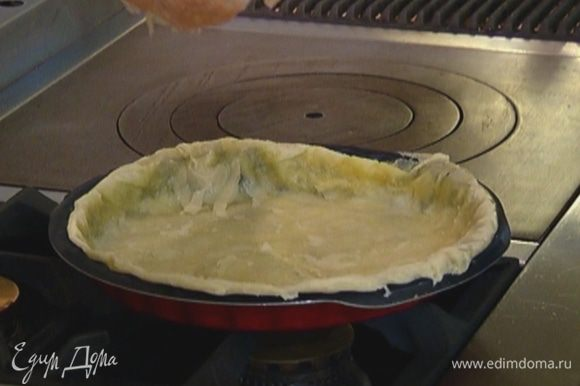 Выложить тесто вместе с бумагой в форму так, чтобы бумага оказалась сверху, сделать из теста бортики, насыпать сверху горох или крупу и отправить в разогретую духовку на 15 минут.