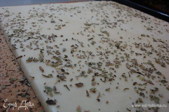 Рабочую поверхность посыпать смесью трав и спецций. Затем на нее выложить слоеное тесто и раскатать его скалкой в тонкий пласт с одной стороны и другой так, чтобы все спецции остались на нем.