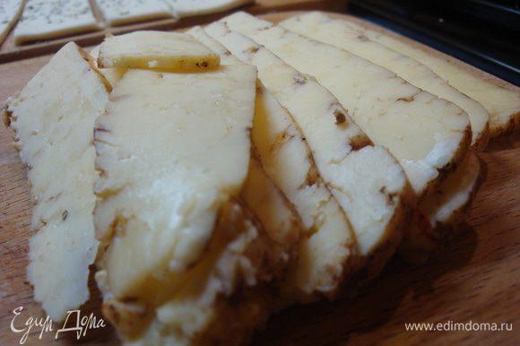 Раскатанное тесто нарезать острым ножом на равные длинные полоски шириной примерно 4-5 см. Твердый сыр нарезать тонкими кусочками по длине крабовых палочек.