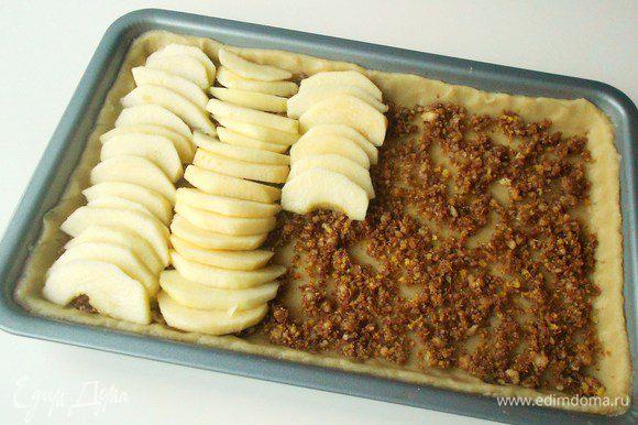 Тесто часто наколоть вилкой и равномерно распределить по нему ореховую смесь. Сверху уложить яблочные дольки. Выкладывайте рядами в противоположных направлениях. Это не принципиально, но смотрится в итоге эффектнее!