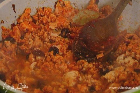 Фарш выложить к луку с чесноком, посолить, поперчить и перемешать, добавить тмин, гвоздику, изюм, оливки и, помешивая, обжарить почти до готовности, затем влить 50 мл горячей воды, еще раз перемешать и оставить на медленном огне на несколько минут.