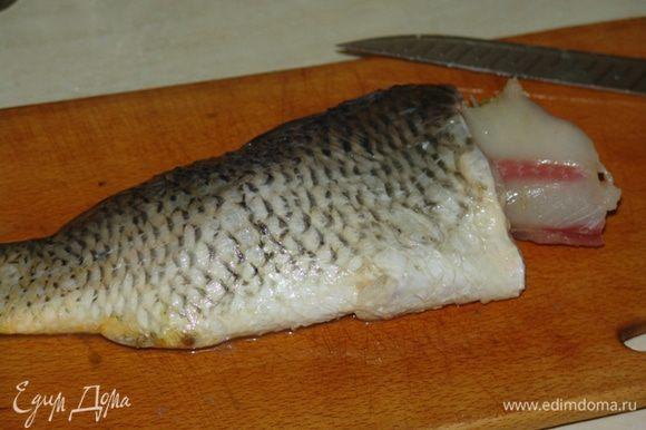 Рыбу почистить (брюшко не разрезать), плавники не вырезать, голову отделить, жабры удалить (если планируете подавать рыбу целиком). По кругу сделать надрезы, отделяя шкуру от мяса, оставляя немного мяса на шкуре. Снятую мякоть разберите, удаляя кости. Чтобы мясо легче отделялось от костей, кости можно обдать кипятком. Мясо мелко порубить ножом.