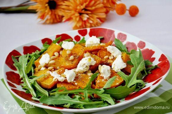На порционную тарелку выложить листья руколы, тёплую тыкву,творожный сыр, посыпать кедровыми орешками, полить маслом, которое осталось после запекания тыквы. Очень вкусное сочетание, попробуйте! Приятного аппетита!